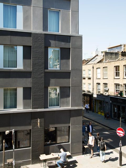 Redchurch Street, Shoreditch, Refurbishment and extension of Hotel Corner building using black concrete and brick piers. Ground floor retail units contain J Crew and Allpress coffee.