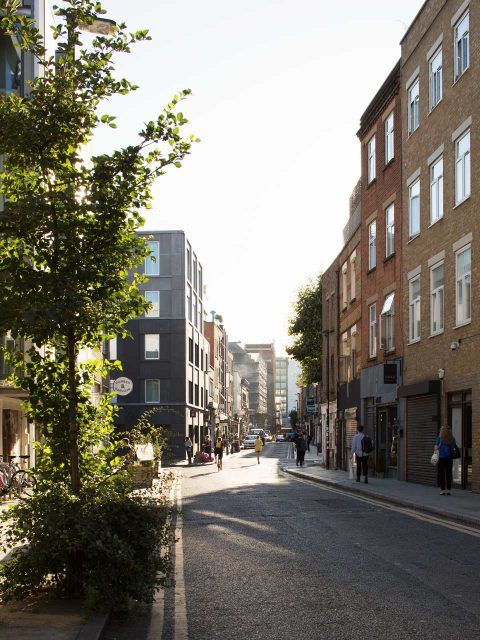 Redchurch Street, Shoreditch, Refurbishment and extension of a new hotel corner building using black concrete and brick piers. Ground floor retail units contain J Crew and Allpress coffee.
